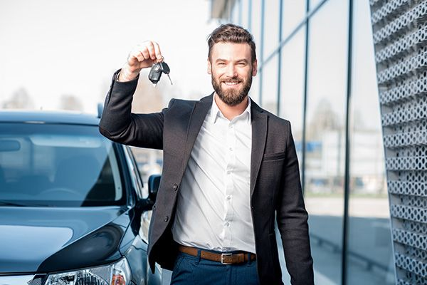 A smiling man with car keys in hand.
